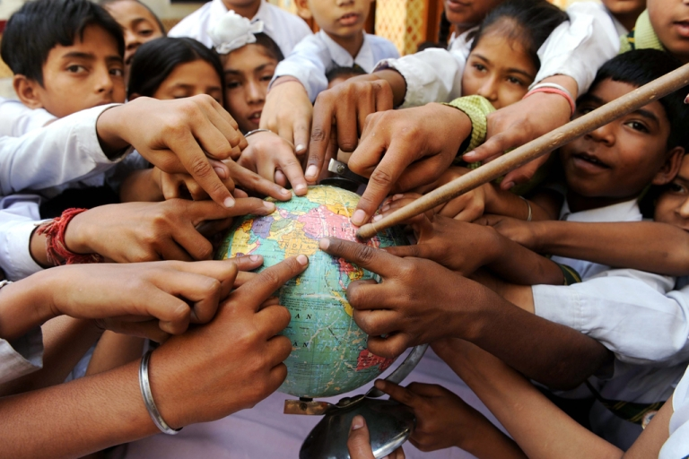 <p>Indian school children in Amritsar point to India on a globe on Earth Day, April 22, 2010.</p>