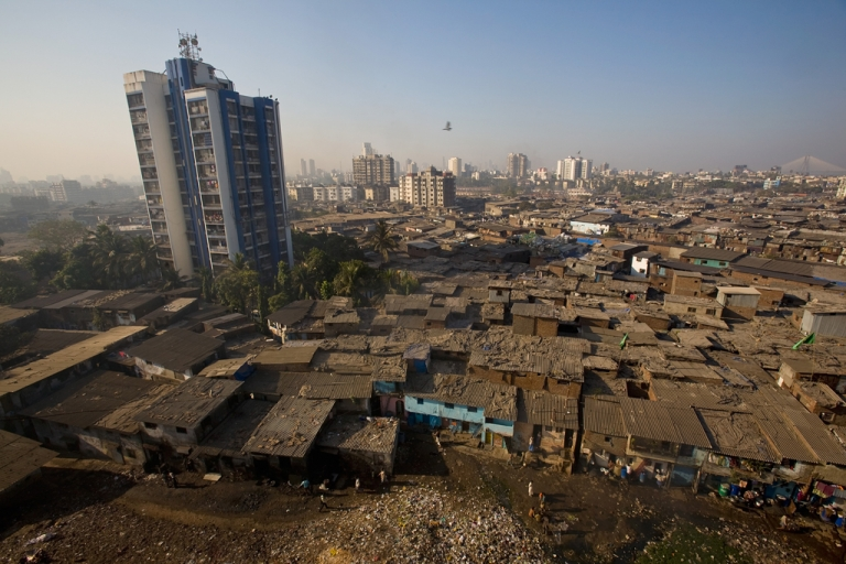<p>Men recycle waste on rooftops in Dharavi slum on Feb. 3, 2009 in Mumbai.</p>