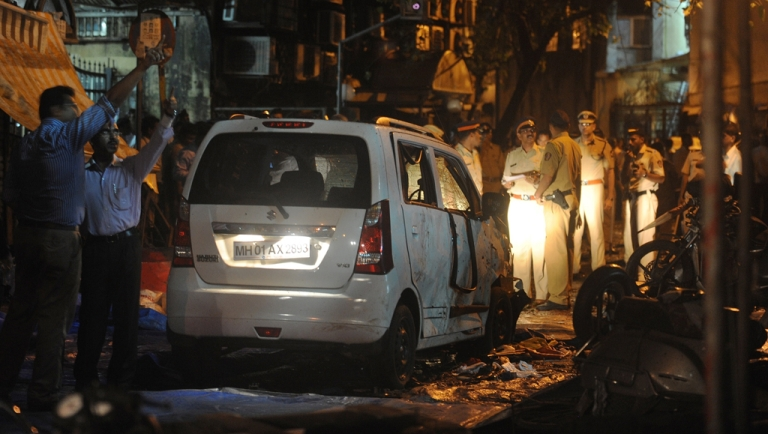 <p>Indian security officials gather around a damaged vehicle at a bomb blast site at the Opera house area of Mumbai on July 13, 2011.</p>