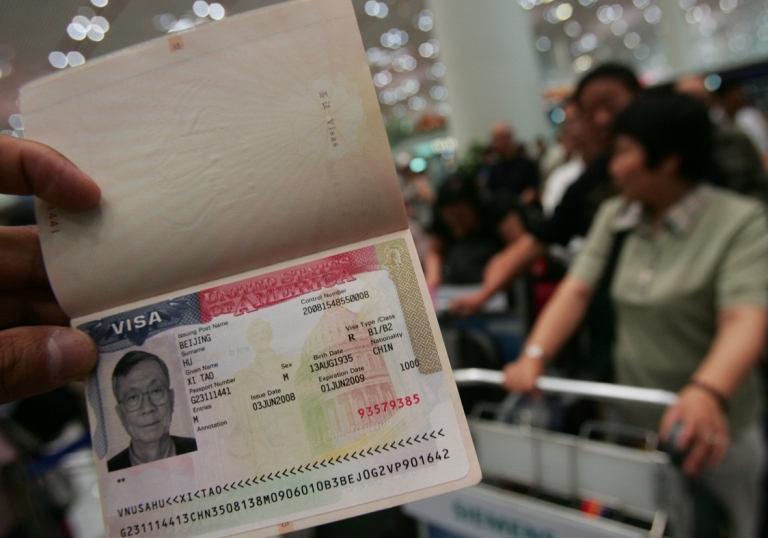 <p>A man in Beijing displays his visa for the United States.</p>