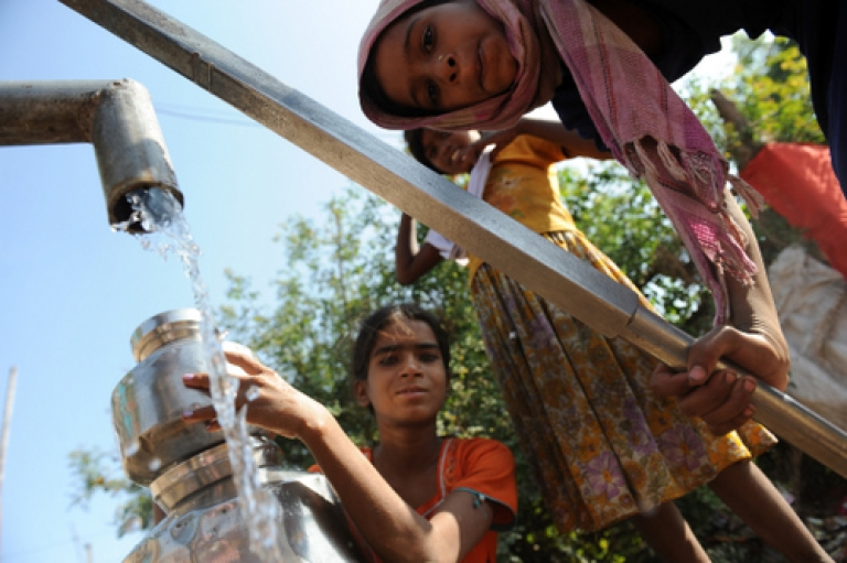 <p>Residents of an Indian slum collect water from a hand pump. The World Bank estimates that 21% of communicable diseases in India are related to unsafe water, while diarrhea alone causes more than 1,600 deaths daily.</p>