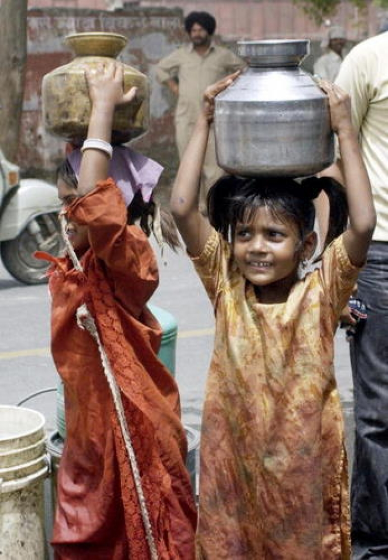 <p>Children carry water pots filled from a government water supply tank in New Delhi. Many Indians have limited access to clean drinking water.</p>