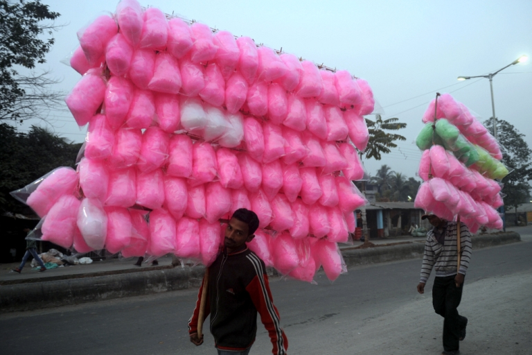 <p>Indian vendors carry cotton candy in Siliguri on November 25, 2012. India's economy logged around 5.5 percent growth in the last financial quarter, the finance minister estimated on November 24, 2012.</p>