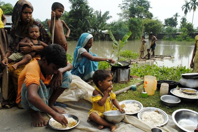 <p>An Indian family eats alongside a road after their house was washed away by flood waters at Bulut Village, some 30 km away from Guwahati on June 30, 2012. Torrential monsoon rains triggered floods which swamped villages in eastern India and forced at least 2 million people to leave their homes for higher ground.</p>