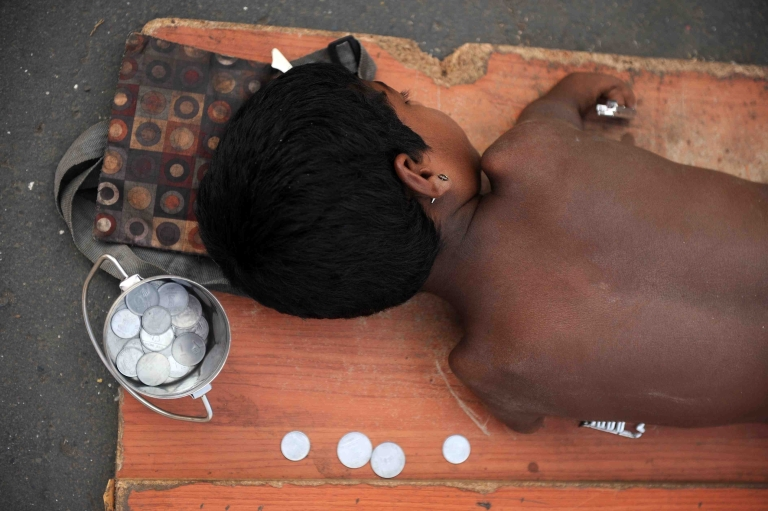 <p>A handicapped child lies on a mat while begging for alms next to a few Indian rupee and paise coins given to him in Mumbai on December 7, 2011. Though it has plenty of problems at home, India initiated a global aid agency endowed with $15 billion for the next five years.</p>