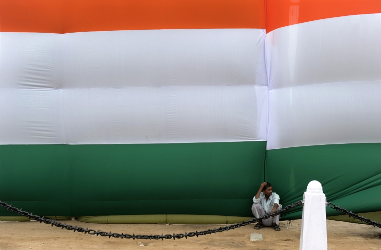 <p>An Indian man sits in the shade of a huge Indian flag adorning the India Gate monument in New Delhi during Independence day celebrations on August 15, 2012. Indian Premier Manmohan Singh used his Independence Day speech to promise to improve conditions for foreign investment in the country after a sharp downturn in economic growth.</p>