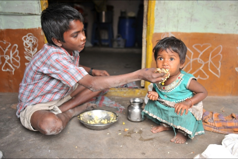 <p>An Indian boy feeds his sister at their home in a slum in Hyderabad, on January 10, 2012. Levels of under-nutrition in the country are 'unacceptably high' despite impressive GDP growth, which is just one reason why charities are concerned that the UK's decision to withdraw millions of pounds of funding by 2015 is premature.</p>