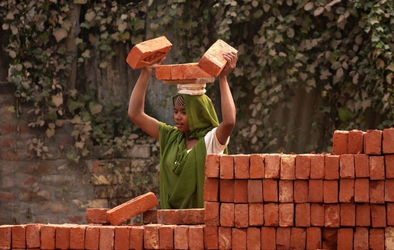 <p>A young Indian labourer carries a load of bricks as she works on a construction site in Allahabad on November 16, 2012. According to a new study, India will become the world's second-most competitive country in the brick-and-mortar manufacturing sector over the next five years.</p>