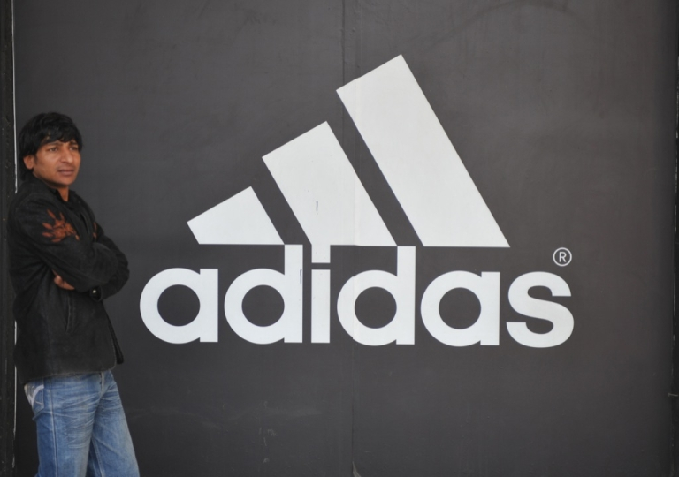 <p>An Indian man stands next to the Adidas logo near the Adidas store in New Delhi on January 11, 2012.</p>
