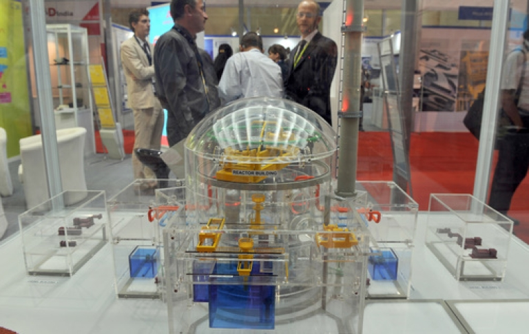 <p>Delegates of the India Nuclear Energy 2011 summit interact as they stand behind a scale model of a nuclear reactor in Mumbai on September 29, 2011. Prime Minister Manmohan Singh wooed investments from South Korea and India unveiled massive spending plans for nuclear energy this week amidst continued protests against a nuclear power plant in Kudankulam, Kerala.</p>