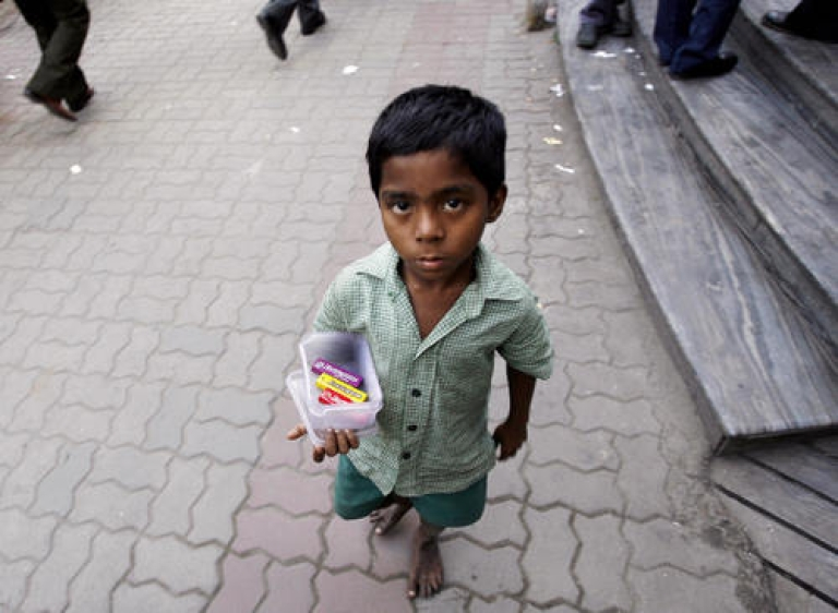 <p>An Indian street child sells chewing gum outside a shopping plaza in Kolkata. In a bid to fight hunger, the worst evil of such poverty, the government on Friday introduced a bill to provide subsidized food grain to two-thirds of the population. Critics say the plan will cause distortions in the commodities market and result in a disastrous increase in the deficit. But proponents say no cost is too great.</p>