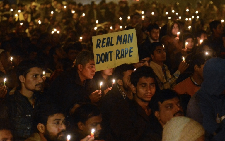 <p>Male Indian protestors hold candles and a sign that reads