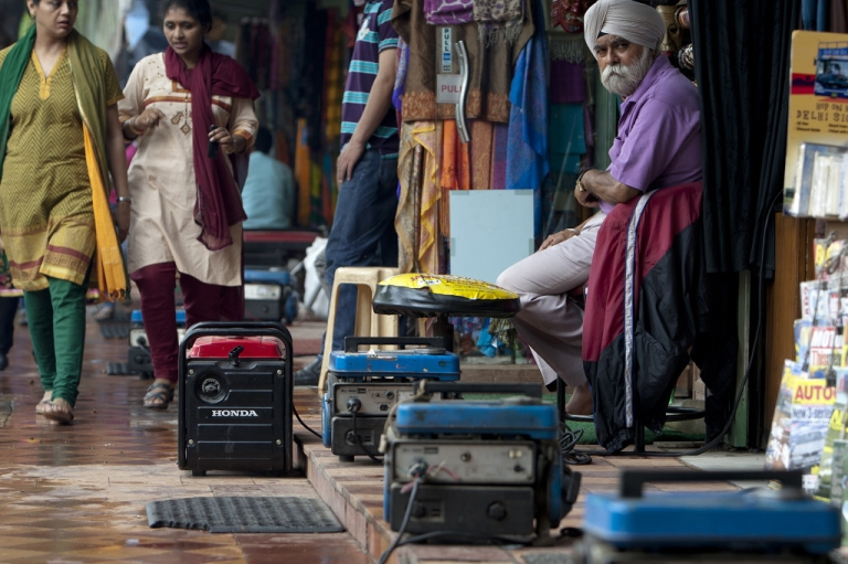<p>Portable power generators (C) provide electrical power to souvenir shops along Janpath Market, a popular tourist shopping area, during a power outtage in New Delhi on July 31, 2012.</p>
