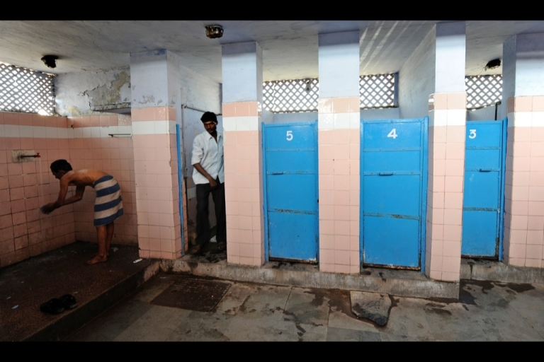 <p>An Indian man (L) washes as another comes out of a toilet in a toilet complex run by an NGO Sulabh International at railway station in New Delhi on April 23, 2011.</p>