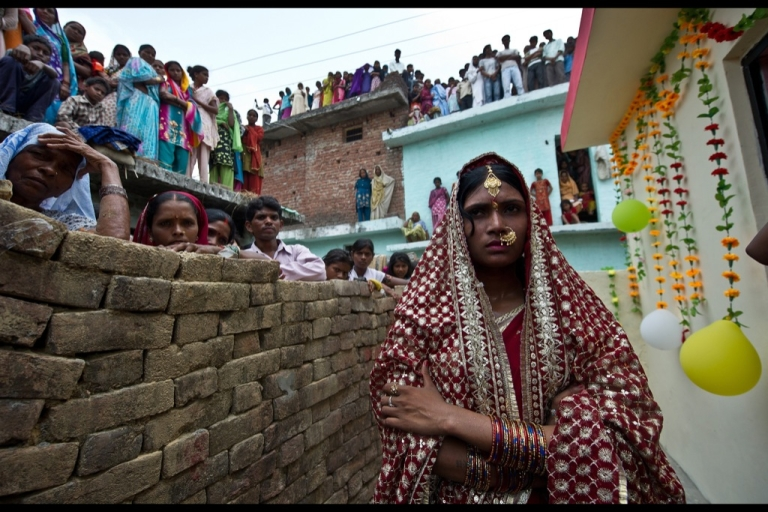 <p>Neighbours watch as recently-wed Priyanka Bharti, who left her marital home in protest due to the lack of toilets in the household, return to the residence of her in-laws at Vishnupur village in Maharaj Ganj. Three newly-wed brides who left their marital homes because of sanitation concerns were each rewarded with 200,000 rupees (3,500 USD) and the costruction of new toilets in their in-laws residences for taking a stand on sanitation in rural India.</p>