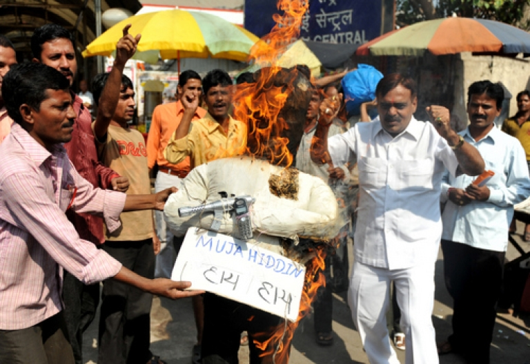 <p>Activists from India's Congress Party shout slogans as they burn an effigy representing the 'Indian Mujahideen' organisation during a protest in Mumbai on Decemeber 8, 2010.</p>