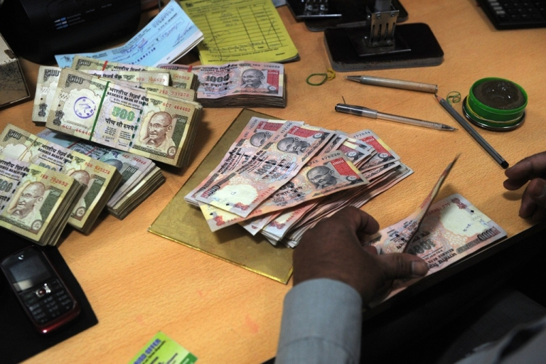 <p>An employee counts Indian rupee notes at a bank in Mumbai on May 16, 2012.</p>