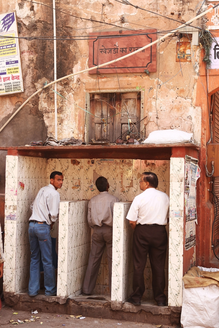 <p>Men use a public urinal at the local markets in Jaipur, India.</p>