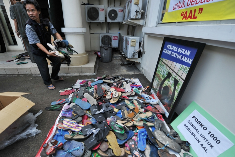 <p>An official from Indonesia's Child Protection Commission carries sandals they received by package at their office in Jakarta on Jan. 4, 2012.</p>