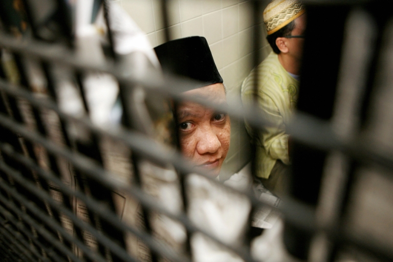 <p>The leader of Islamic militant network Jemaah Islamiyah (JI) Zarkasi peers out of a cell at a court, before his first trial in Jakarta, Dec. 17, 2007.</p>