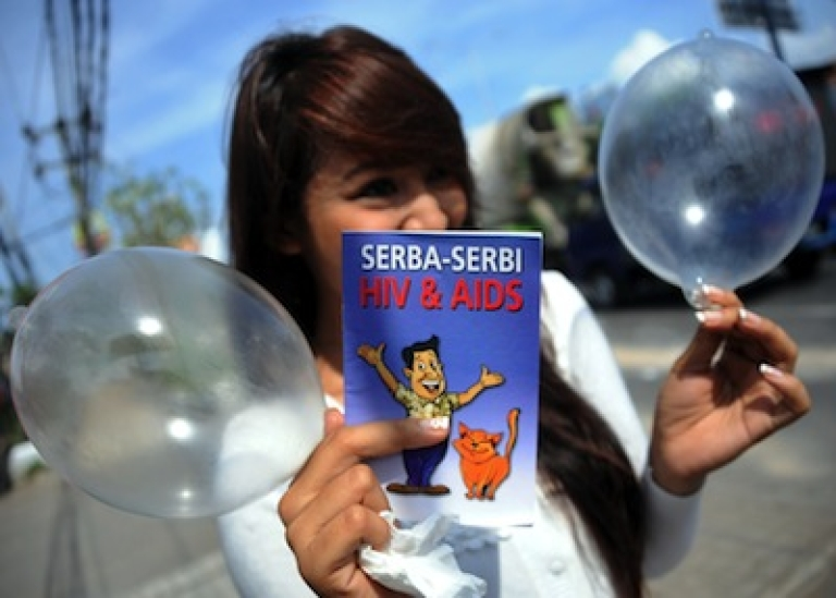 <p>A woman displays inflated condoms during a World Aids Day campaign in Bali island on December 1, 2012.</p>