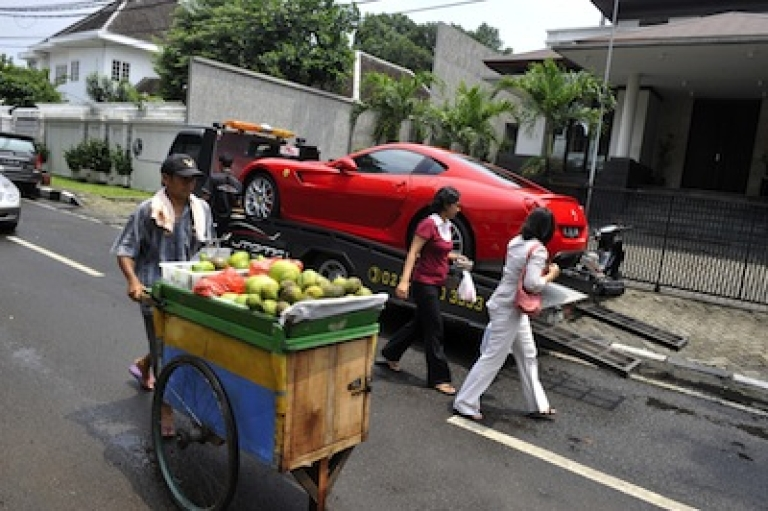 <p>A street vendor pushes his cart past a luxury Ferrari sports car being delivered to the residence of a wealthy Indonesian resident at the affluent Menteng district in Jakarta on February 16, 2010.</p>