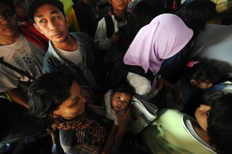<p>People queue to enter a train station in Jakarta on August 25, 2011. Millions of Indonesian Muslims are heading home to their villages to celebrate the Eid al-Fitr holidays with relatives.</p>