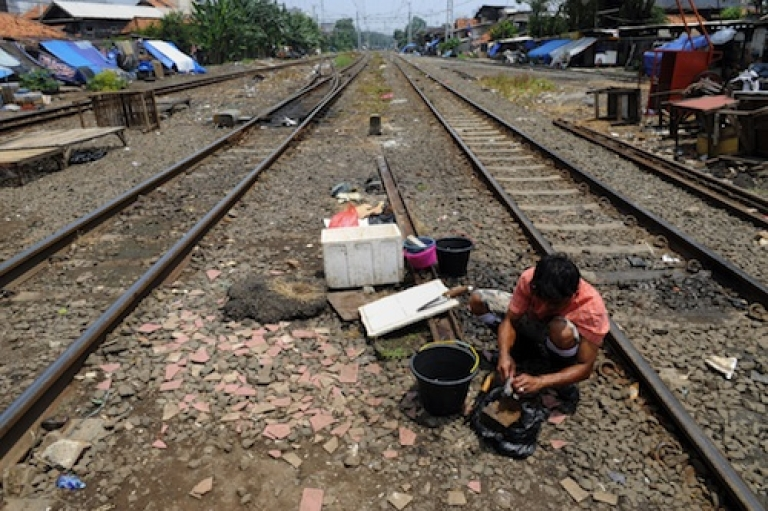 <p>A vendor cleans fish amongst the railroad tracks in Jakarta on September 28, 2010. Some sick residents of West Jakarta have taken to lying across railroad tracks in hopes the electric current will somehow cure their ailments. The practice has spread to Malaysia.</p>