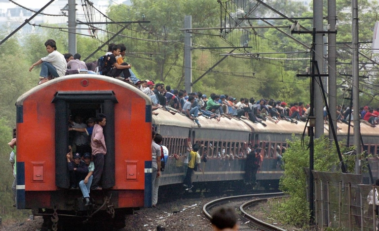 <p>Commuters sit on top of a train as it pulls out of Palmerah station during rush hour in Jakarta, 29 June 2004.</p>