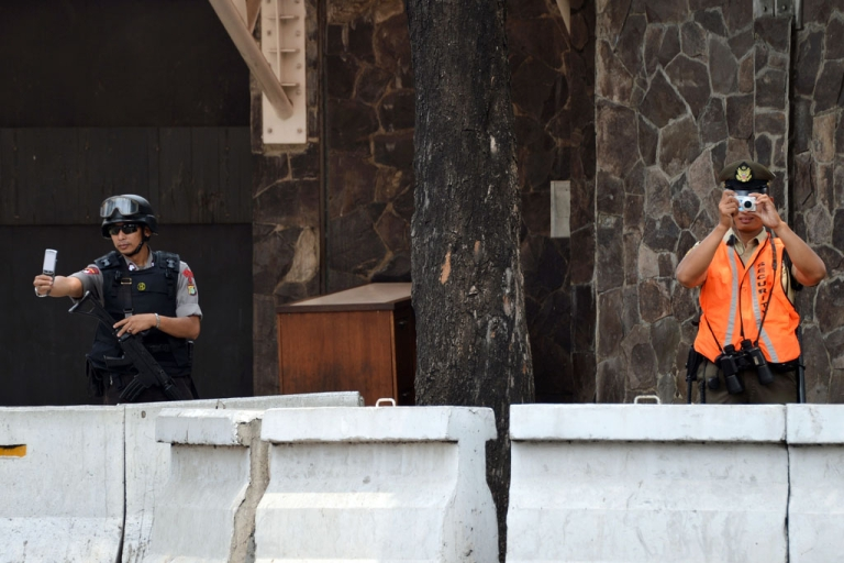 <p>An embassy guard and an Indonesian policeman take photographs while protesters mark the anniversary of the 9/11 attacks outside the US embassy in Jakarta on September 11, 2012.</p>