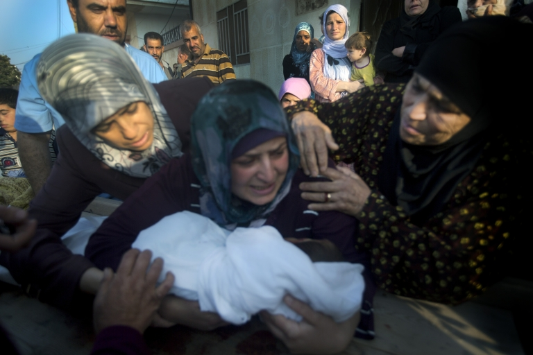 <p>A mother holds the body of her 5 year-old son during his funeral after he was killed by a sniper outside the city of Homs.</p>