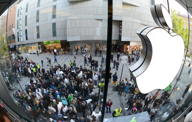 <p>Customers queue to enter the Apple Store where a giant logo is displayed in the southern German city of Munich on September 21, 2012 as the iPhone 5 goes on sale.</p>
