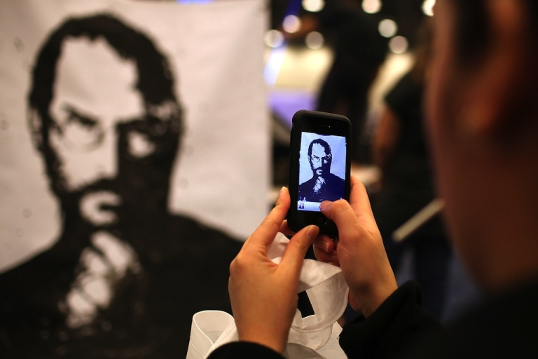 <p>An iPhone user photographs a painting of former Apple CEO Steve Jobs during the Macworld iWorld Expo at the Moscone Convention Center on January 26, 2012 in San Francisco, California.</p>