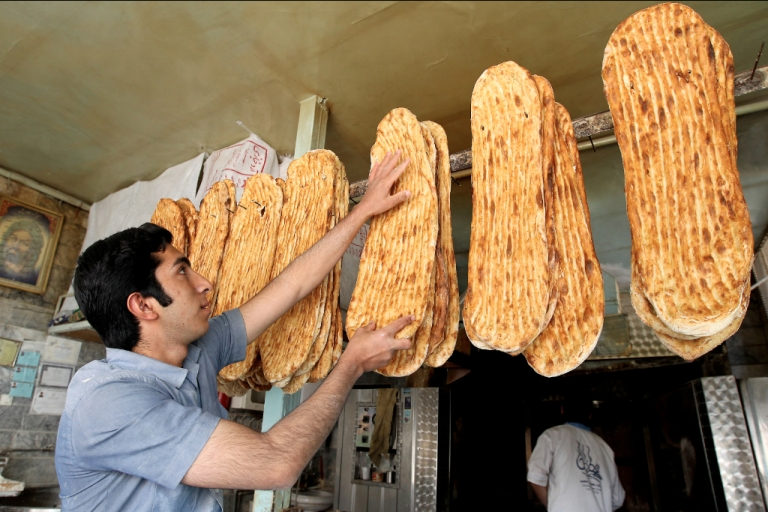 <p>An Iranian baker displays loaves of bread at a bakery in central Tehran.</p>