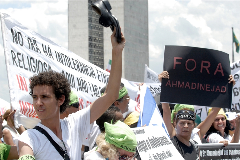 <p>A demonstrator raises a shoe during a protest against the last visit of Iran's President Mahmoud Ahmadinejad in Brasilia, while he met then-President Luiz Inacio Lula da Silva (not in frame) on November 23, 2009.</p>