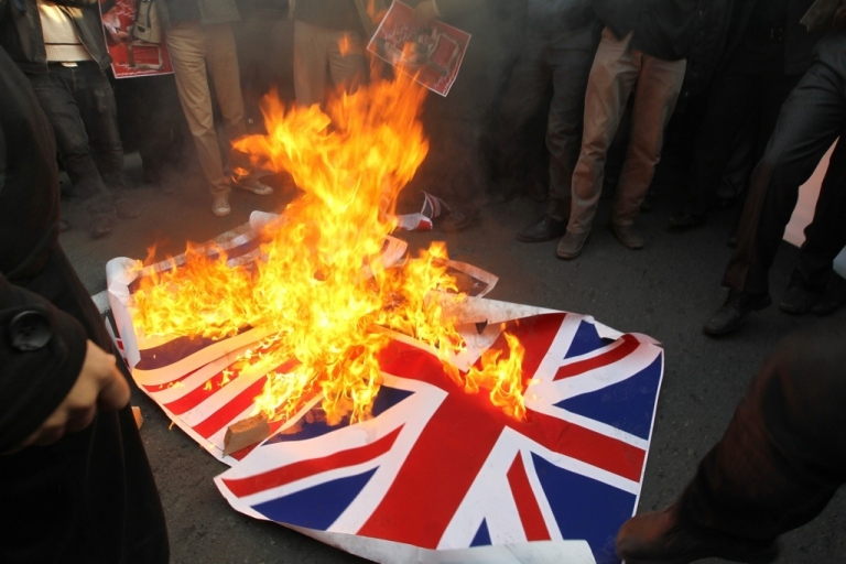 <p>Iranian protesters burn the British flag outside the embassy in Tehran on Nov. 29, 2011.</p>