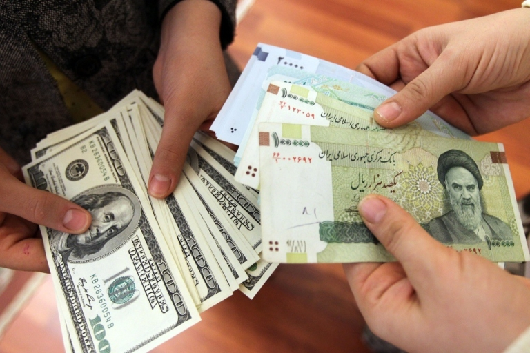 <p>Iranians count and exchang United States dollars and Iranian rial banknotes. The value of the rial has plunged in recent weeks.</p>