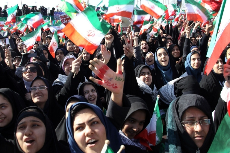 <p>Iranian women wave national flags during a rally to mark the 33rd anniversary of the Islamic revolution in Azadi Square in Tehran on Feb. 11, 2012.</p>