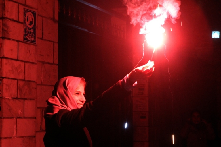 <p>An Iranian woman holds a firecracker in Tehran on March 13, 2012 before the Spring holiday of Nowruz. While Nowruz is often a time for Iranians to travel abroad, this year economic sanctions, a devalued currency and international tensions are keeping them home.</p>
