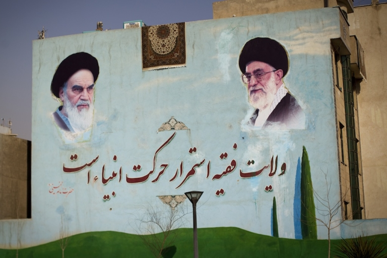 <p>A washed carpet hangs from the roof of a building painted with a mural of the late founder of Islamic republic, Ayatollah Ruhollah Khomeini (L) and supreme leader, Ayatollah Ali Khamenei (R) are seen south of Tehran on Feb. 28, 2012.</p>