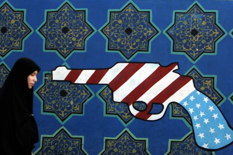 <p>An Iranian woman walks past a mural painting of a revolver on the walls of the former US embassy in Tehran.</p>