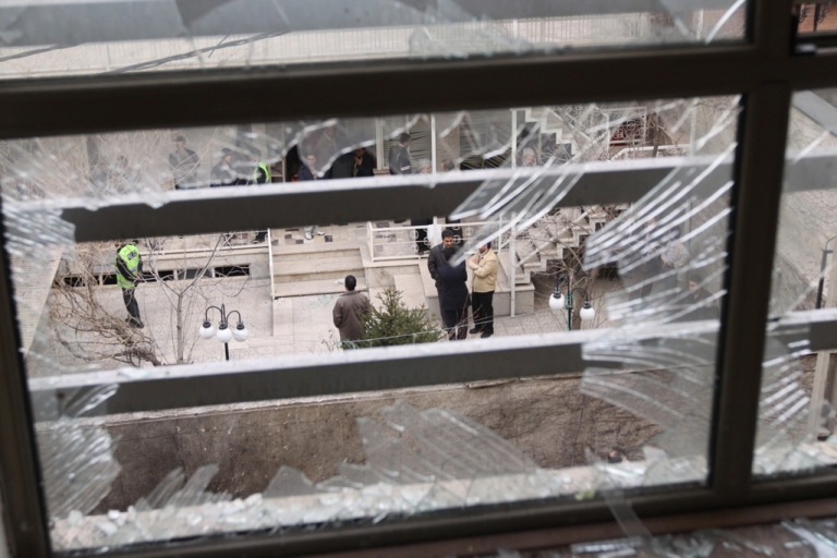 <p>Iranian security agents are seen through a shattered window at the scene of a remote-controlled bomb explosion in which an Iranian university lecturer was killed outside his Tehran residence on January 12, 2010.</p>