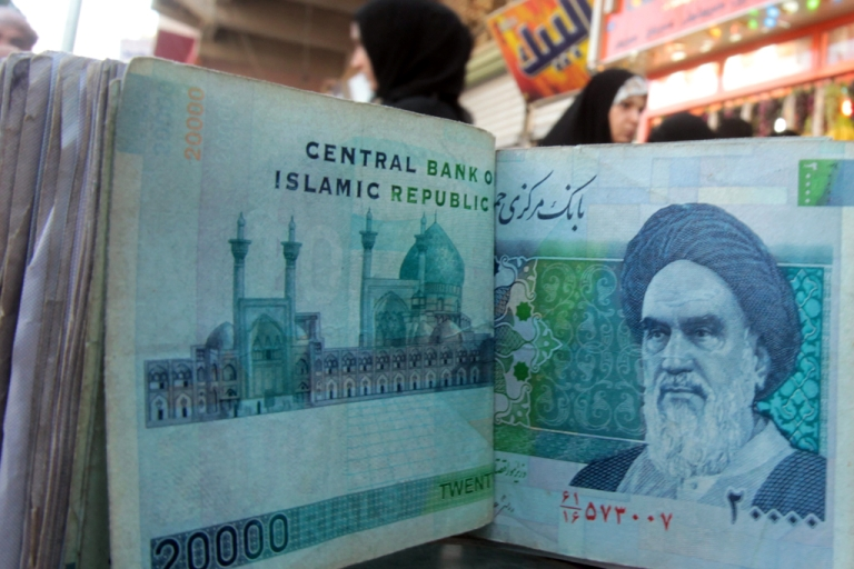 <p>An Iraqi money dealer counts Iranian rial banknotes bearing a portrait of the late founder of the Islamic Republic of Iran, Ayatollah Ruhollah Khomeini, at an exchange office in Baghdad on February 3, 2012.</p>