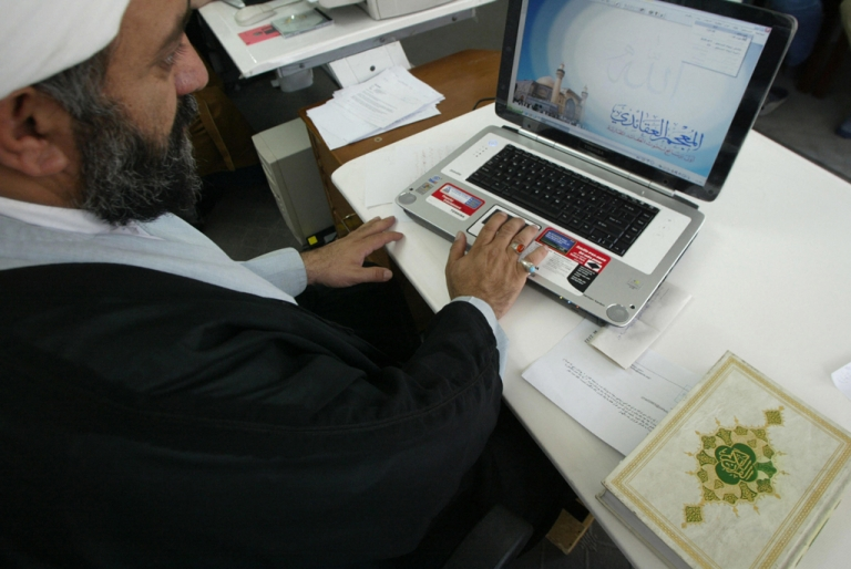 <p>Iranian clergyman Nematollah Daneshmand works on his laptop with a copy of the Koran next to him at his office in Qom. The country has disrupted internet access ahead of national elections next week.</p>