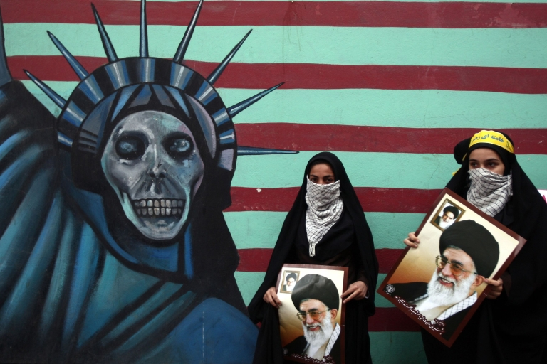 <p>Iranian women hold pictures of Supreme Leader Ayatollah Khamenei outside the former U.S. embassy in Tehran on November 4, 2011, during a rally to mark the storming of the American embassy by Iranian students 32 years ago.</p>