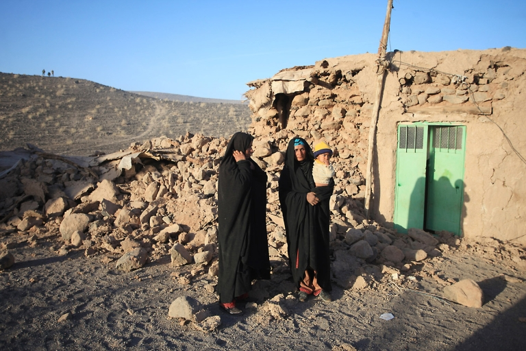 <p>Iranian women and a child stand outside their damaged house in the village of Chah Ghanbar after an earthquake struck southeastern Iran in December 2010.</p>