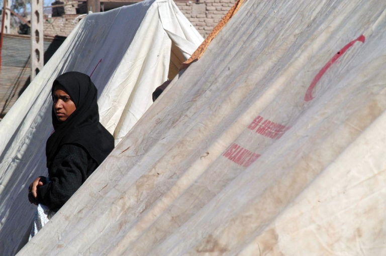 <p>An Iranian woman walks past a tent set up by the Red Crescent January 2, 2003 in Bam, Iran.</p>