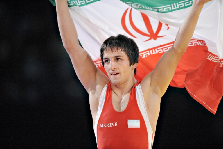 <p>Iran's Hamid Soryan Reihanpour waves the Iranian flag after defeating Armenia's Roman Amoyan in their 55 kg Greco - Roman gold medal match at the World Wrestling Championships in Herning on September 25, 2009.</p>
