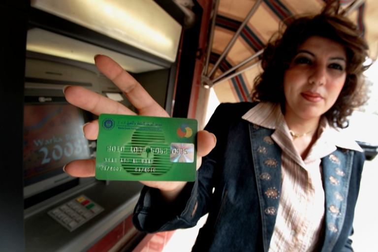 <p>An Iraqi employee of Warka Bank for Investment and Finance shows how to use a credit/debit card that is issued by the bank on March 11, 2008 in Baghdad, Iraq. Warka Bank for Investment and Finance and other Iraqi banks have started issuing credit/debit cards in Baghdad, installing teller machines in selected places in the capital in a move to encourage Iraqis to accept the cards and surmount their repugnance to anything but cash.</p>