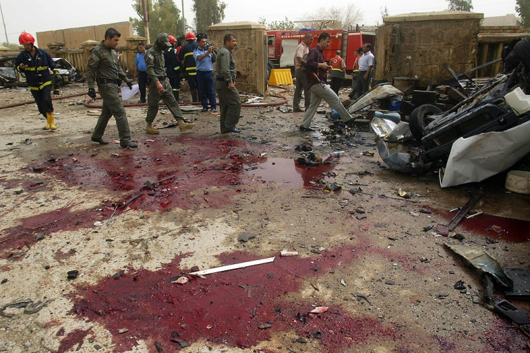 <p>Police inspect the site of one of three bomb attacks in the northern oil-rich city of Kirkuk, Iraq, on May 19, 2011, that killed at least 27 people and wounded 89. Violence has killed more than 460,000 Iraqis since the American invasion in 2003.</p>